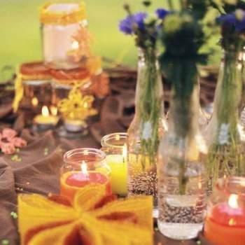 Decoración con velas y botellas de cristal con flores.