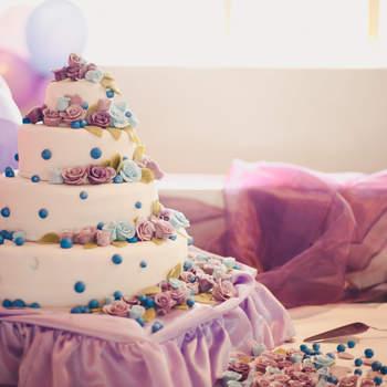 Torta a 4 piani con applicazioni di rose viola,azzurre e rosa e confetti blu