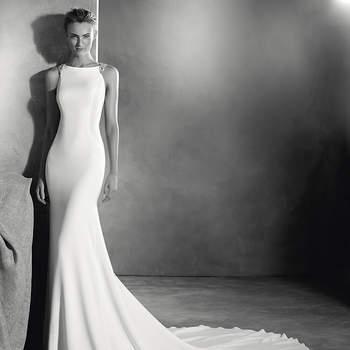 Atrativo vestido de noiva em crepe estilo sereia. Um modelo brilhante graças ao requintado decote de desenho assimétrico adornado com pedraria que converte as costas da noiva numa autêntica joia. Deslumbrante!