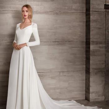 Vestido de novia de manga larga con corte en la cintura y apliques en los hombros y muñeca.