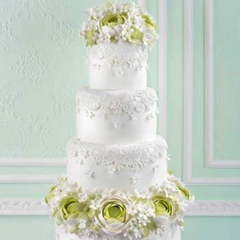 Diseño que reproduce el encaje del vestido de novia decorada con ranúnculos hortensias y jazmines de Madagascar realizados en azúcar.