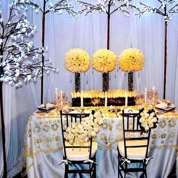 Centros de mesa con rosas amarillo claro, velas, rosas blancas para las sillas, mantel azul aguamarina con pedrería y velas. Es un tipo de decoración muy elegante que está de moda.