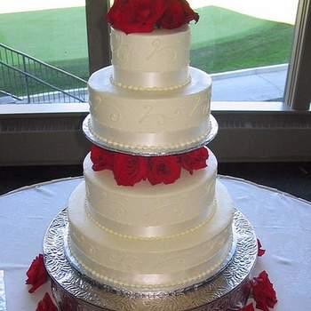 Torta en cuatro pisos con base en acero decorada con rosas.