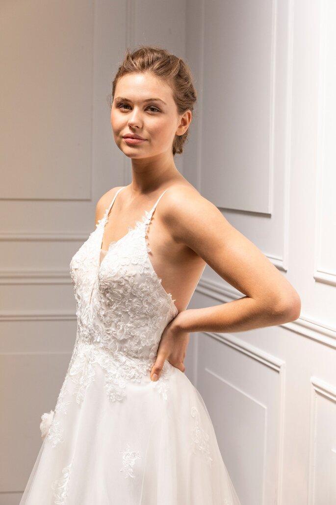 Une mariée les mains sur les hanches, arbore une robe avec de fines bretelles et un bustier brodé de dentelle, un dos nu et une jupe en tulle
