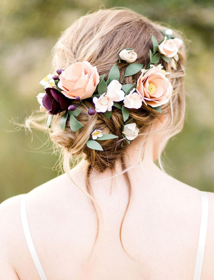 Une mariée avec un chignon déstructuré et des fleurs dans les cheveux