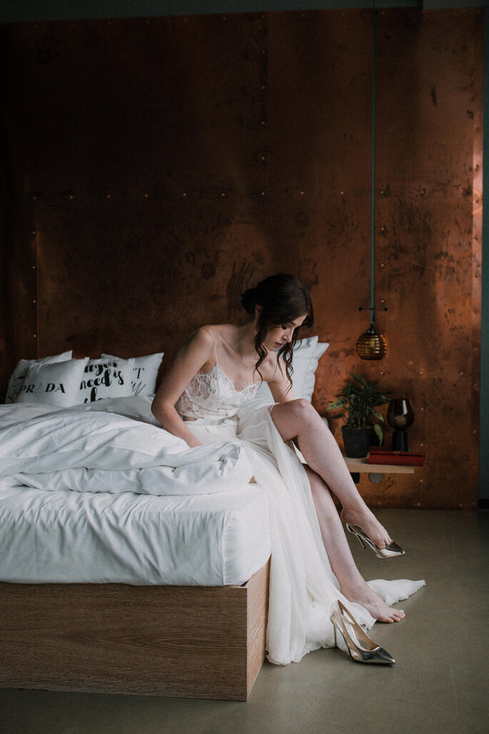Die Braut sitzt auf dem Bett und zieht ihre Hochzeitsschuhe an.