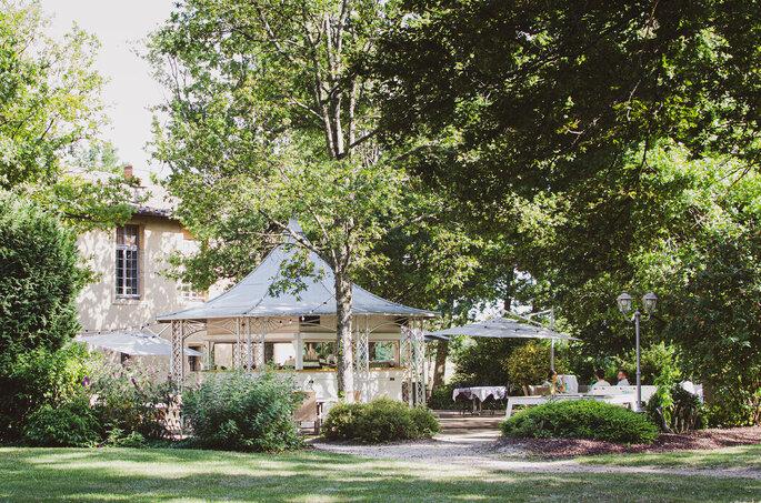 Un chapiteau et un château dans un parc arboré idéal pour une cérémonie laïque de mariage