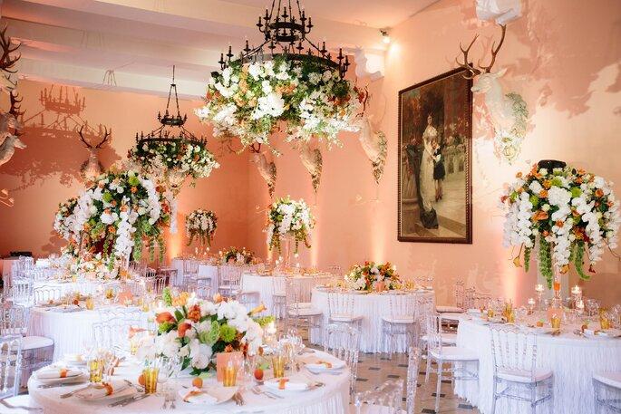 Décoration florale de la salle de réception d'un mariage dans des tons blancs, oranges et verts, esprit bohème
