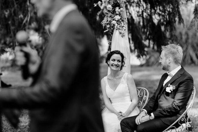 Sourire aux lèvres, une mariée regarde son compagnon pendant la cérémonie laïque.