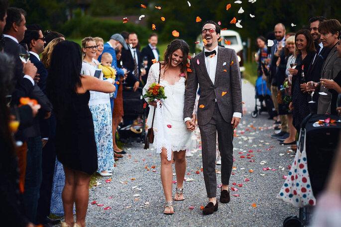 Ein Brautpaar läuft durch eine Menschenmenge in Blütenregen.