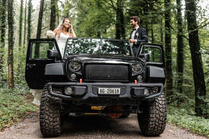 Hochzeitsfoto. Brautpaar auf Jeep im Wald