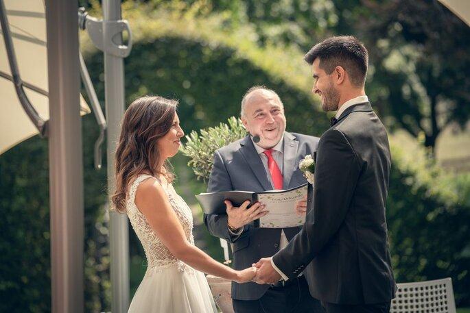 Der Trauredner Hochzeitszeremonien mit Stil Jan Euskirchen hält sein Redenheft in den Händen und hält vor dem Brautpaar lächelnd eine Rede.