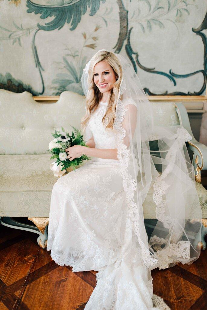 Braut mit Brautstrauß auf Bank im schloss sitzend