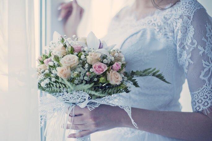 Nouveau Chapitre - Une mariée tenant un bouquet de fleurs roses et corail dans sa main