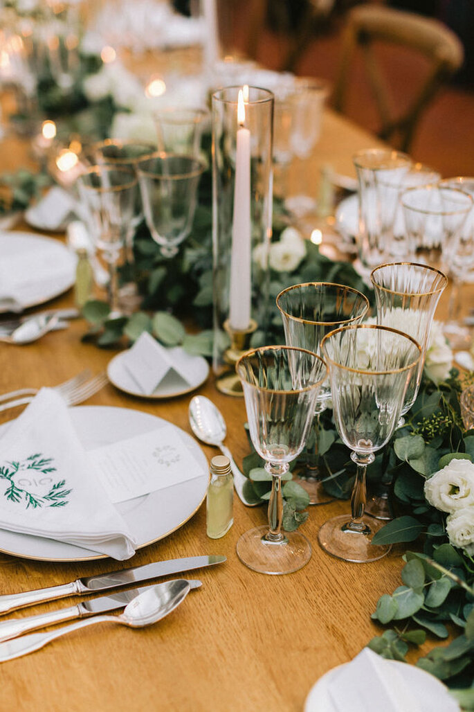 Table dressées pour un mariage avec un chandelier, des verres à bordure dorée et une décoration champêtre