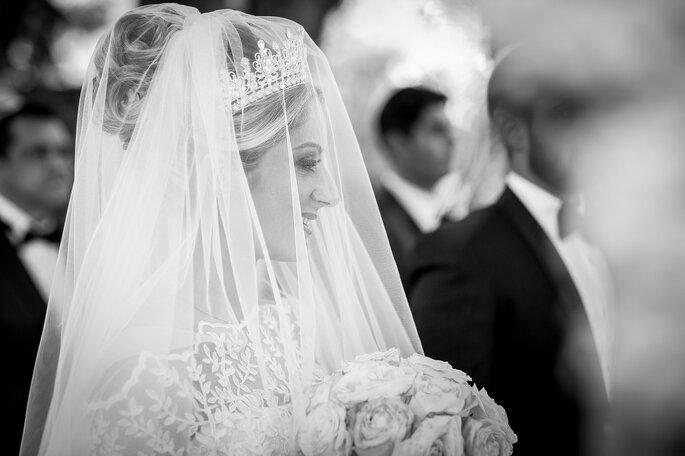 La mariée couverte d'un voile et son bouquet à la main, sourit