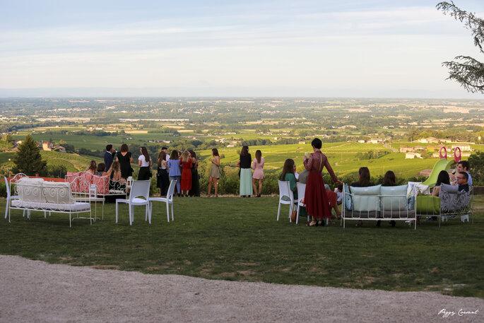 Les invités d'un mariage installés confortablement dans un parc avec une superbe vue sur le Beaujolais