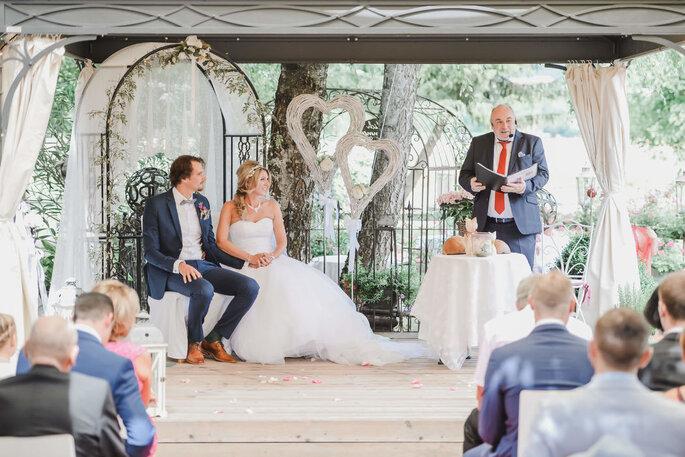 Der Trauredner von Hochzeitszeremonien mit Stil Jan Euskirchen trägt eine Rede vor, neben ihm sitzt das Brautpaar und lächelt.