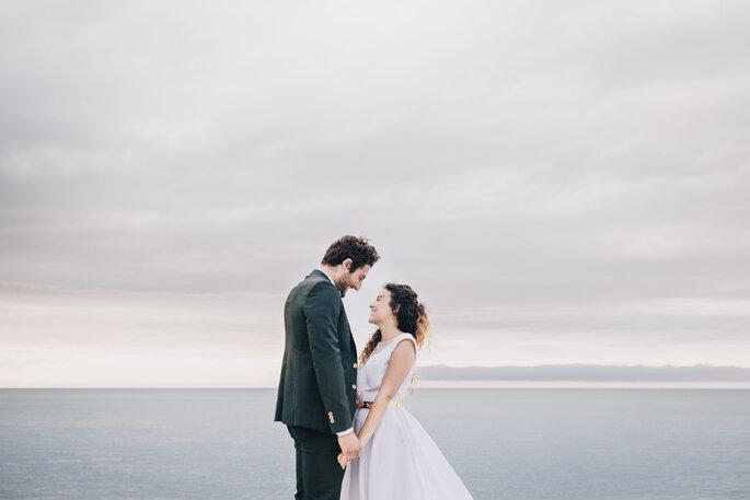 Deux mariés en train de se tenir les mains et de se regarder devant l'océan