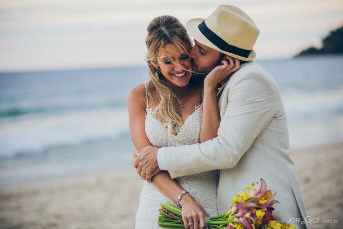 noivos se beijam em praia após o casamento