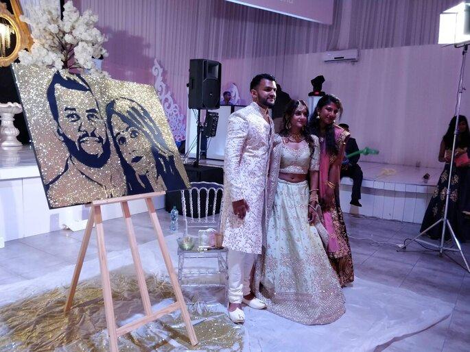 Un couple de mariés accompagné par Sharuki devant un tableau peint par l'artiste