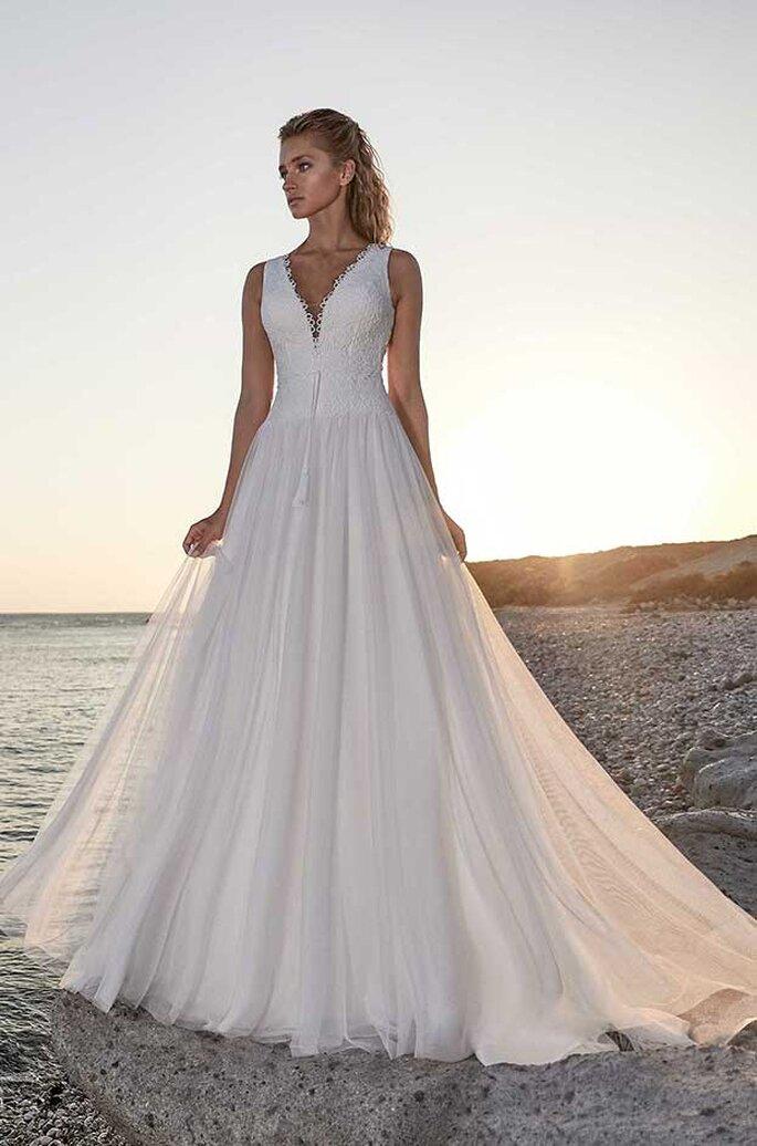 Eine Braut in einem eleganten Brautkleid mit V-Ausschnitt am Strand.