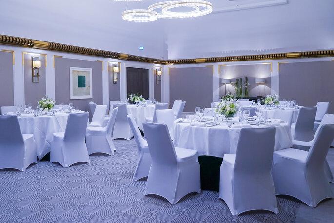Un salon de l'Hôtel Hilton Opéra Paris décoré pour un dîner de réception.
