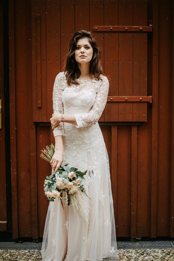 Eine Braut vor einer braunen Holztür. Sie trägt ein bodenlanges Brautkleid mit Spitze.