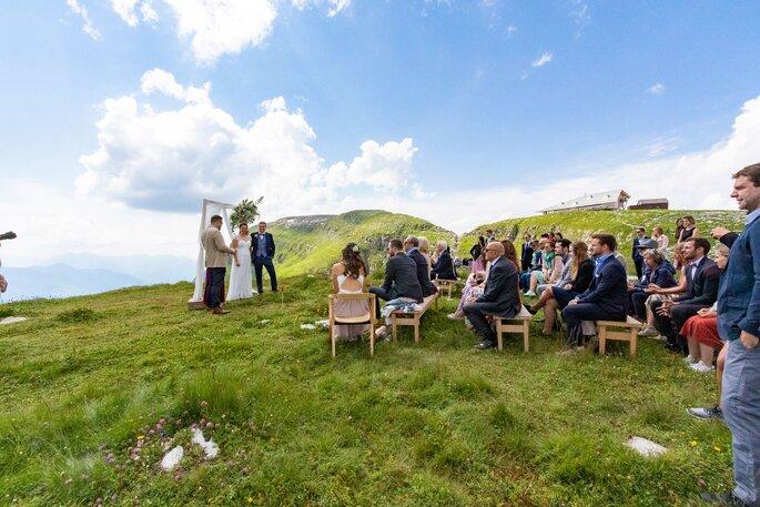 Eine Hochzeitsgesellschaft sitzt auf dem Chäserrugg auf einer Wiese.