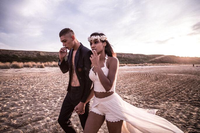 Ein Brautpaar läuft lässig am Strand entlang und raucht.