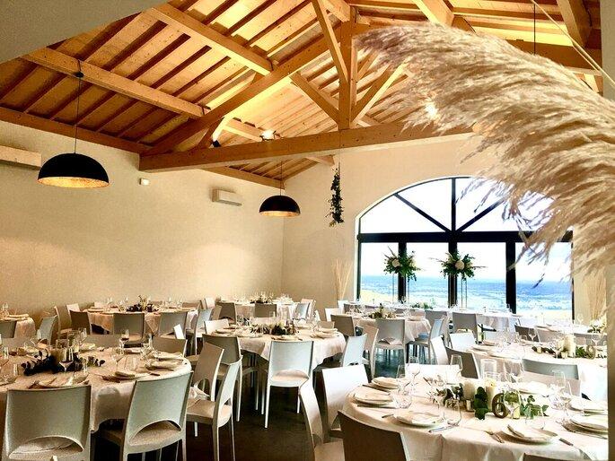 Salle de réception avec de grandes baies vitrées avec vue sur les montagnes