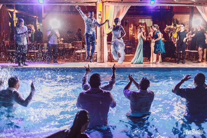 Noivos se jogam na piscina no meio da festa