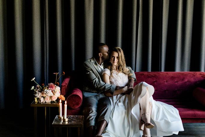 brautpaar sitzt auf einem roten sofa