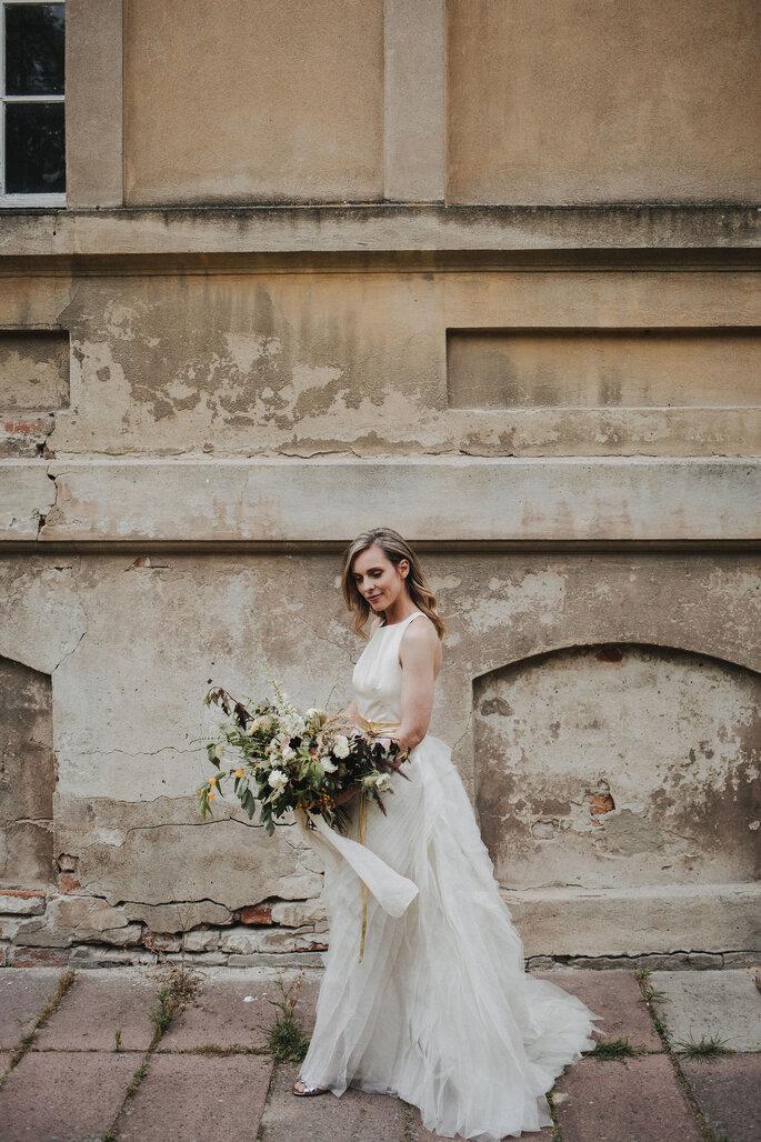 Brautpaar stehend vor Mauer Gebäude