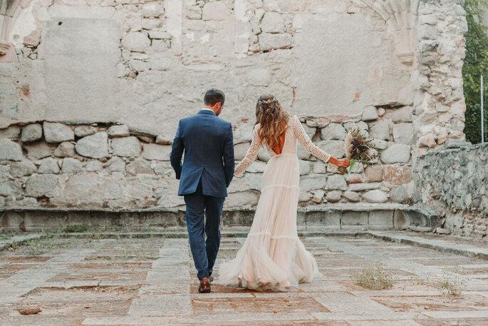 spazierendes Brautpaat mit Rücken zum Fotografen