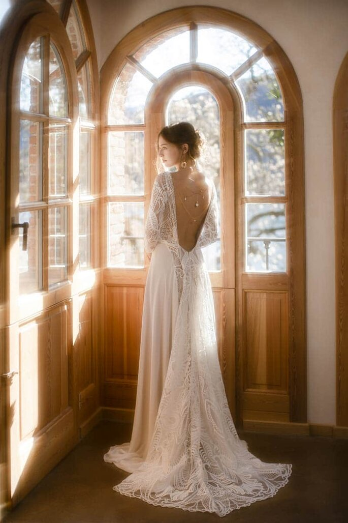 Une mariée arbore une robe dos nu en dentelle de calais