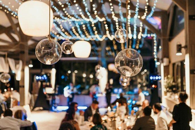 Détails de la décoration du lieu de réception au premier plan, et les invités à tables en arrière plan