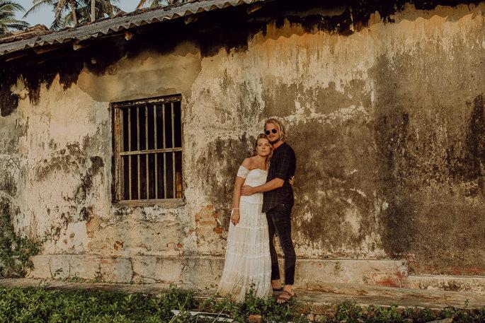 Das Brautpaar steht vor einem alten Gebäude und hält sich in den Armen.