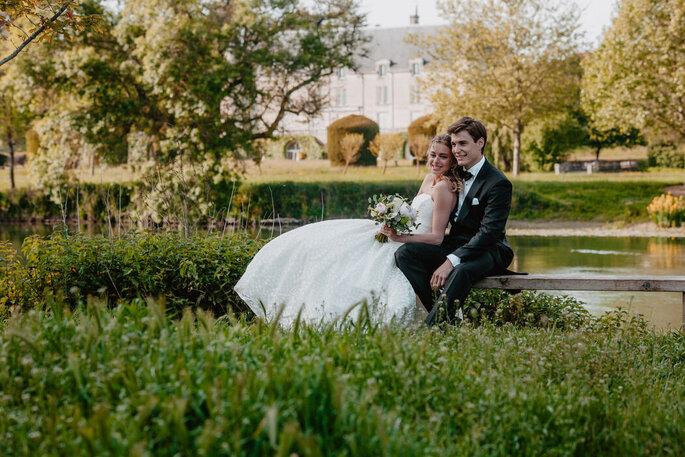 Deux mariés posent dans un jardin bucolique et champêtre