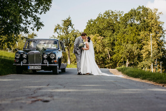 Das Brautpaar beim Shooting mit Hochzeitsauto, Foto von Hüttner Fotografie.