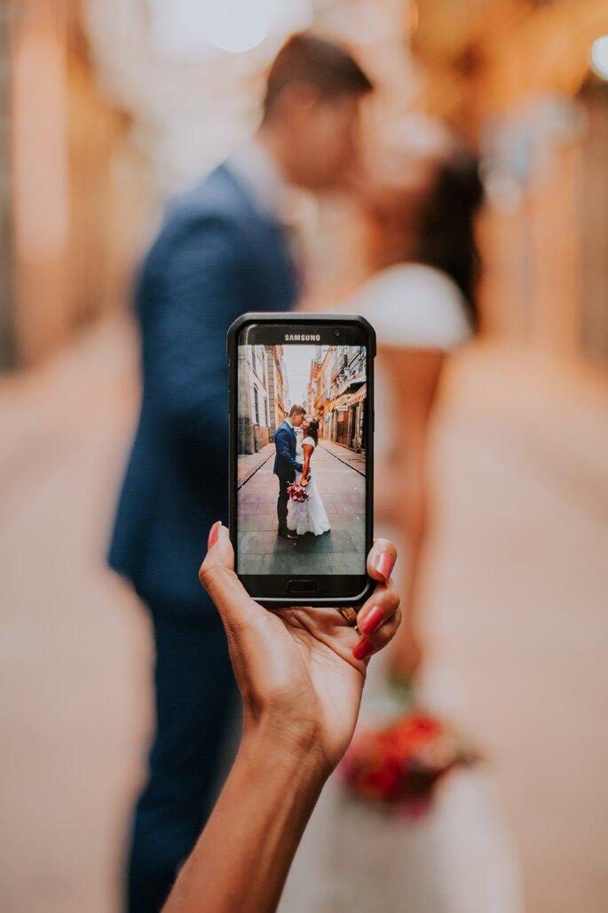 pessoa a pegar num smartphone fotografar noivos