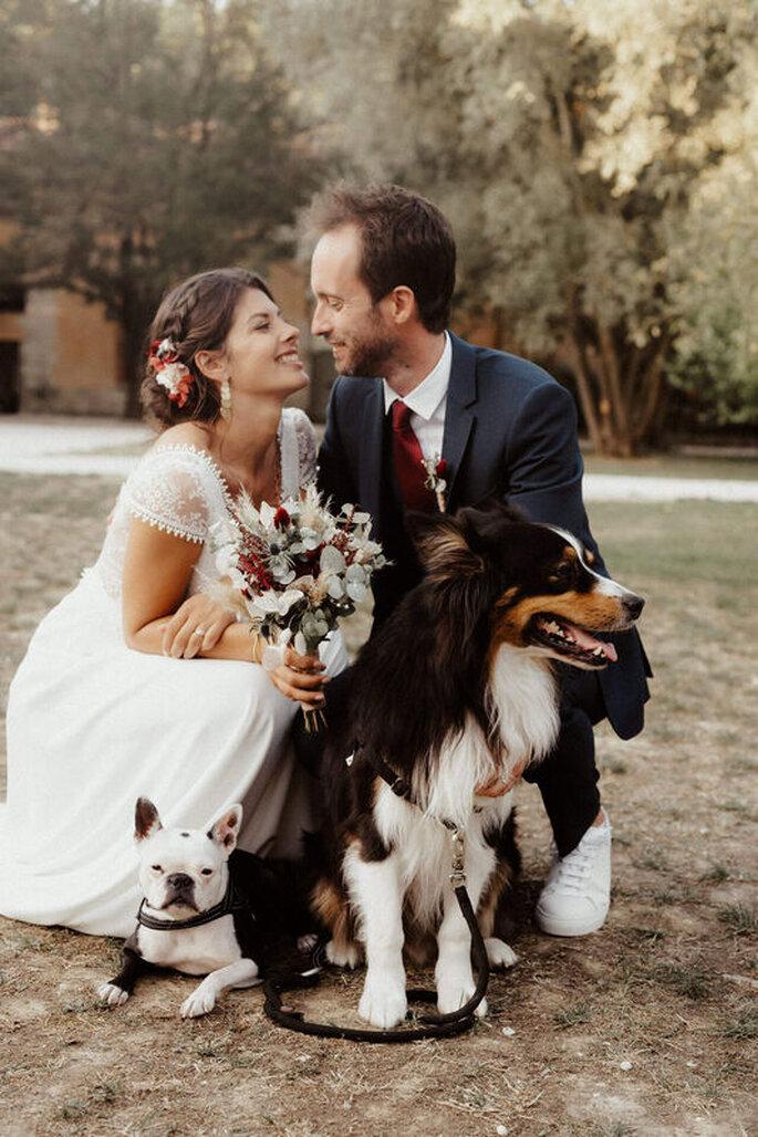 Couple de mariés agenouillés dans un parc en compagnie de leurs chiens