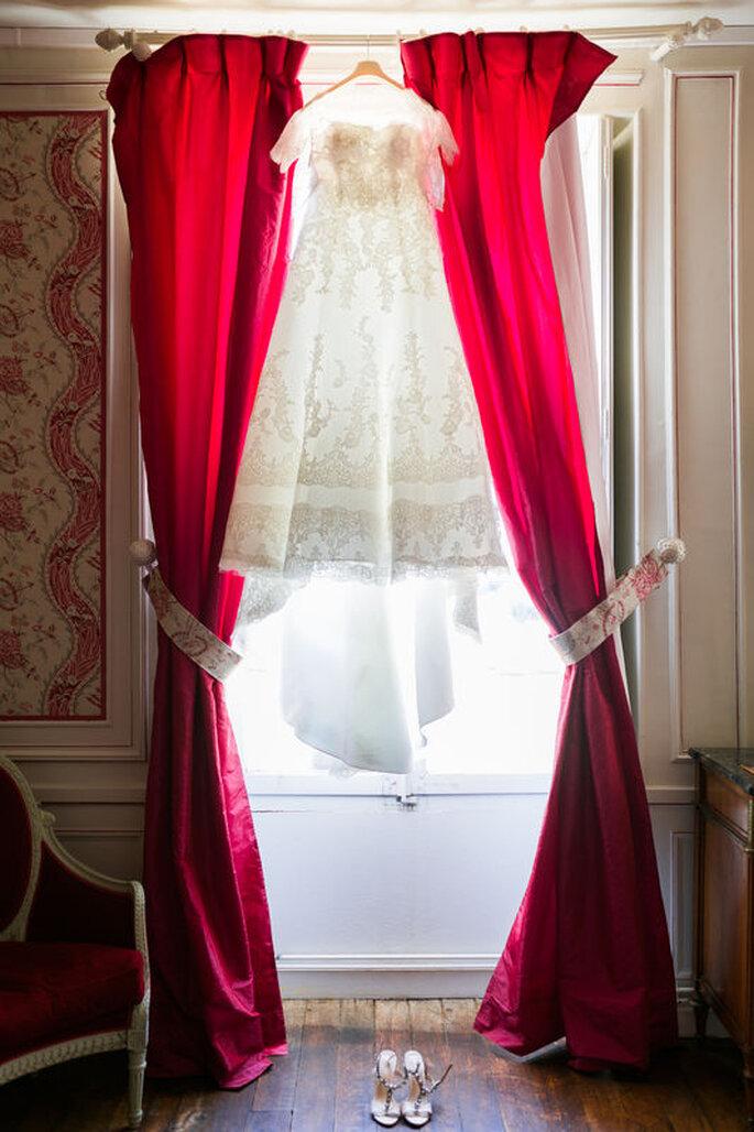 La tenue de la mariée prête à être enfilée dans la suite du château, décorée de rouge