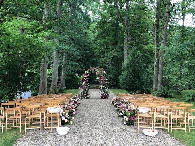 Une cérémonie laïque orchestrée au Manoir Saint Hubert, une arche de fleurs en pleine forêts et des rangés de chaises en bois décorées pour un mariage