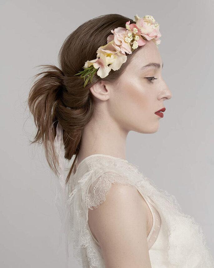 Une coiffure de mariage tendance - La mariée porte une couronne de fleurs qui descend sur son front et un chignon original