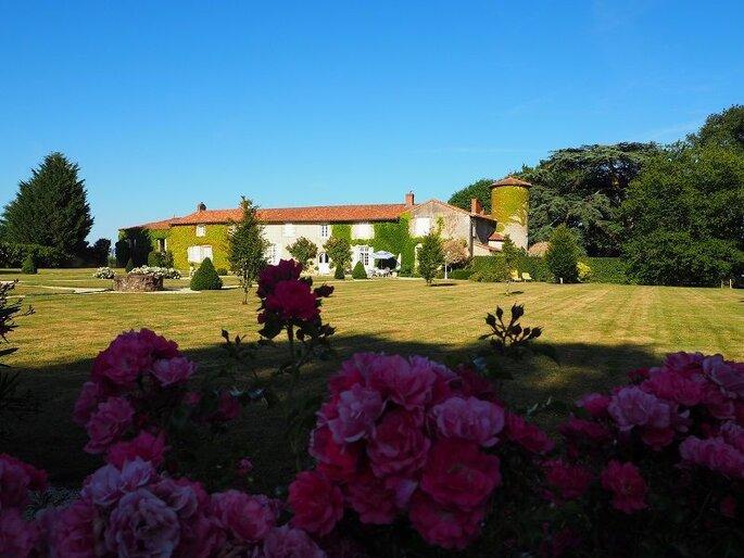 La Seigneurie du Bois Benoist vue de l'extérieur et inscrite dans un véritable écrin de verdure avec des fleurs en premier plan