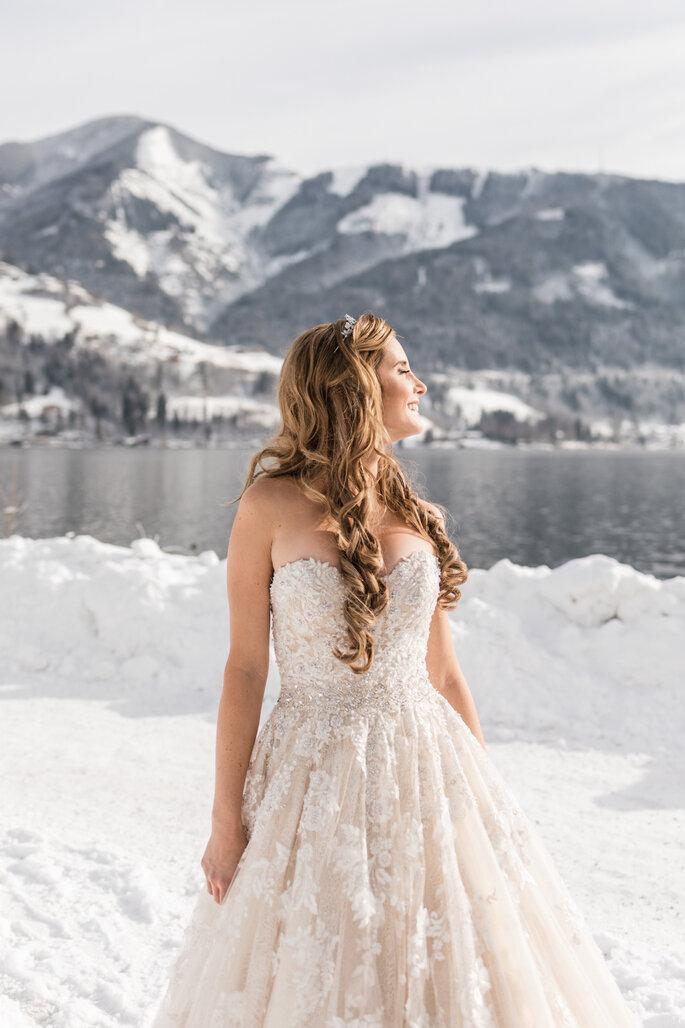 Getting Ready. Braut im fertigen Hochzeitslook im Schnee vor See