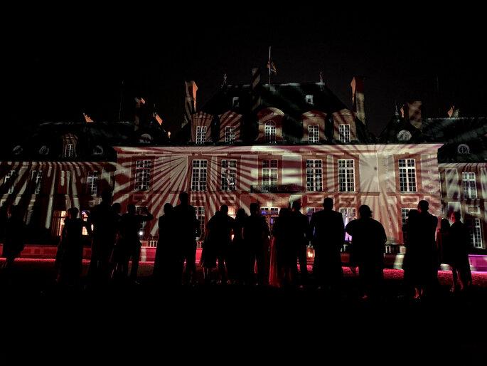 Les invités d'un mariage contemplent une façade illuminée grâce à des jeux de lumière originaux