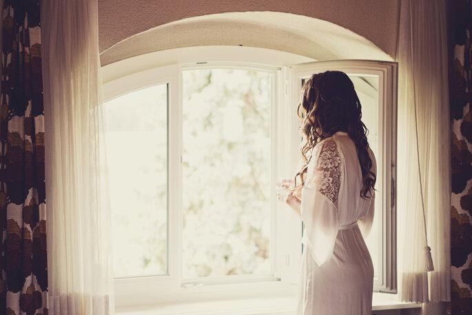 Getting Ready Braut. Braut steht vor Fenster währen Getting Ready