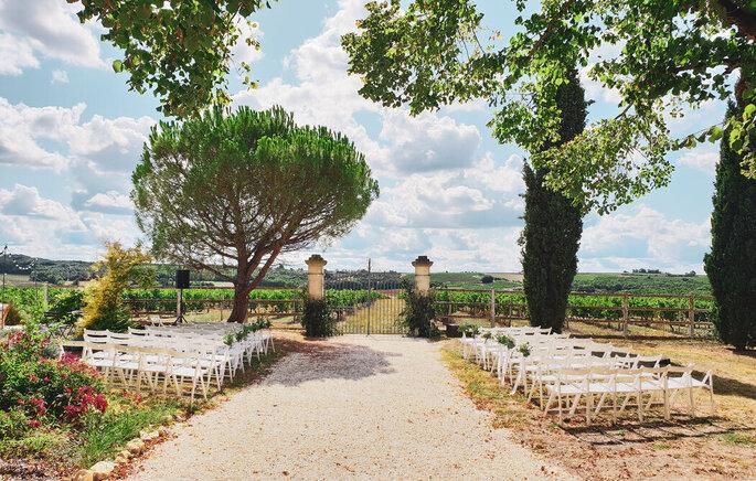 Le cadre d'une cérémonie laïque en extérieur, dans un parc, devant un portail avec un vignoble en toile de fond